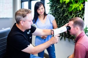 Man taking retinal image using hand held camera